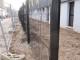 une autre clôture rigide noire en cours de pose